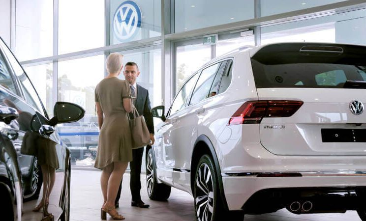 A man and women standing in front of a car